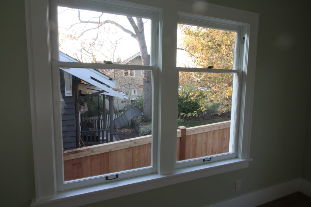 two full restored double hung windows. beautiful. soft lighting. sun going down behind the translucent glass.